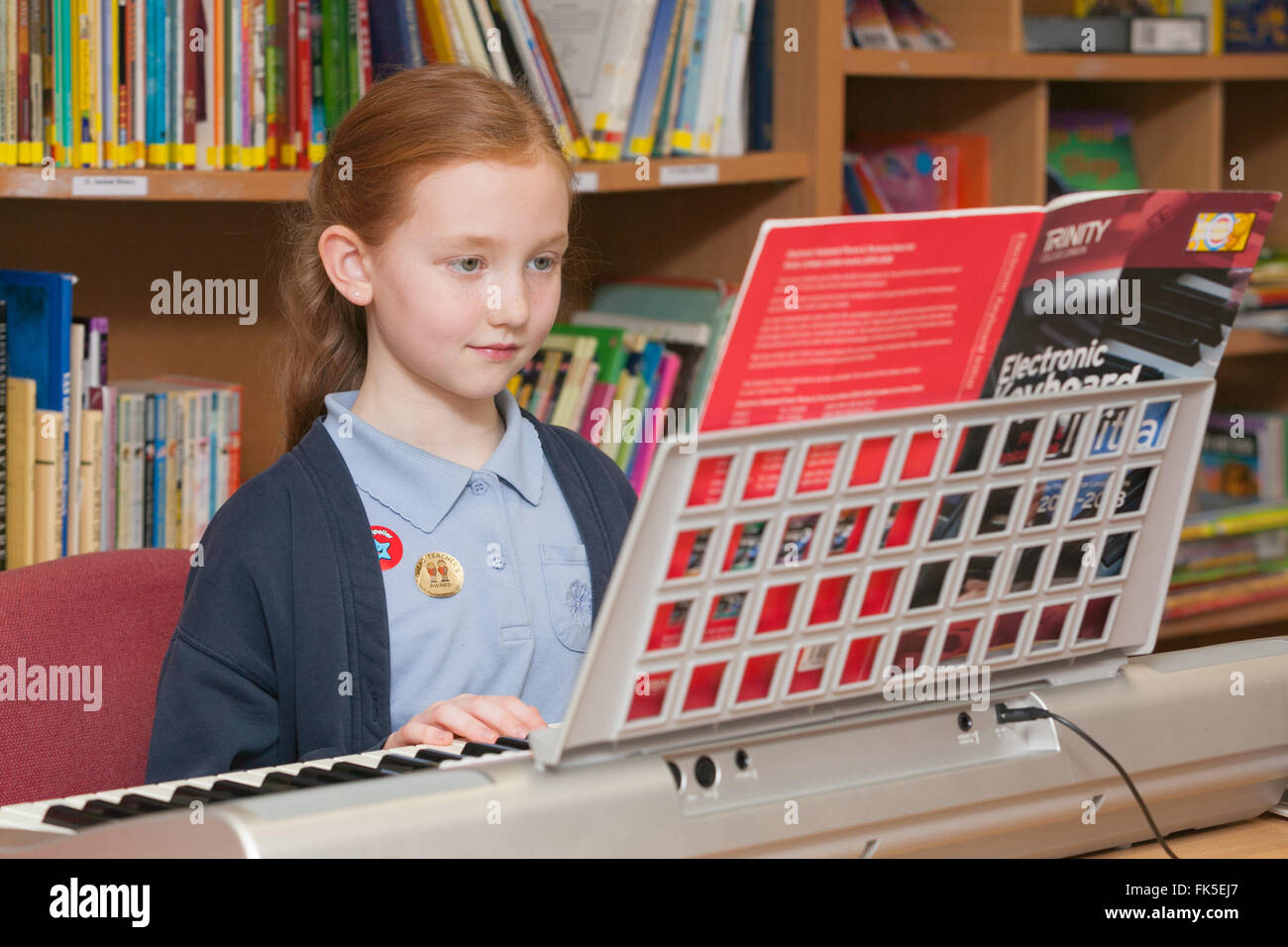 A pupil in school uniform at a Primary School in the UK playing an electronic piano keyboard. - Stock Image