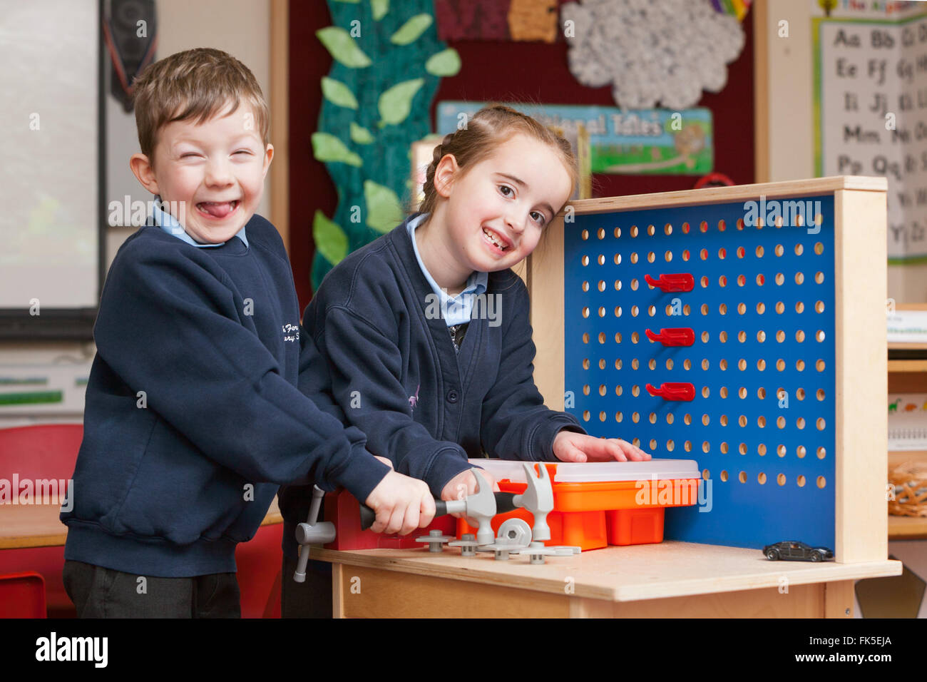 Pupils in school uniform at a Primary School in the UK playing with toy hand tools. - Stock Image