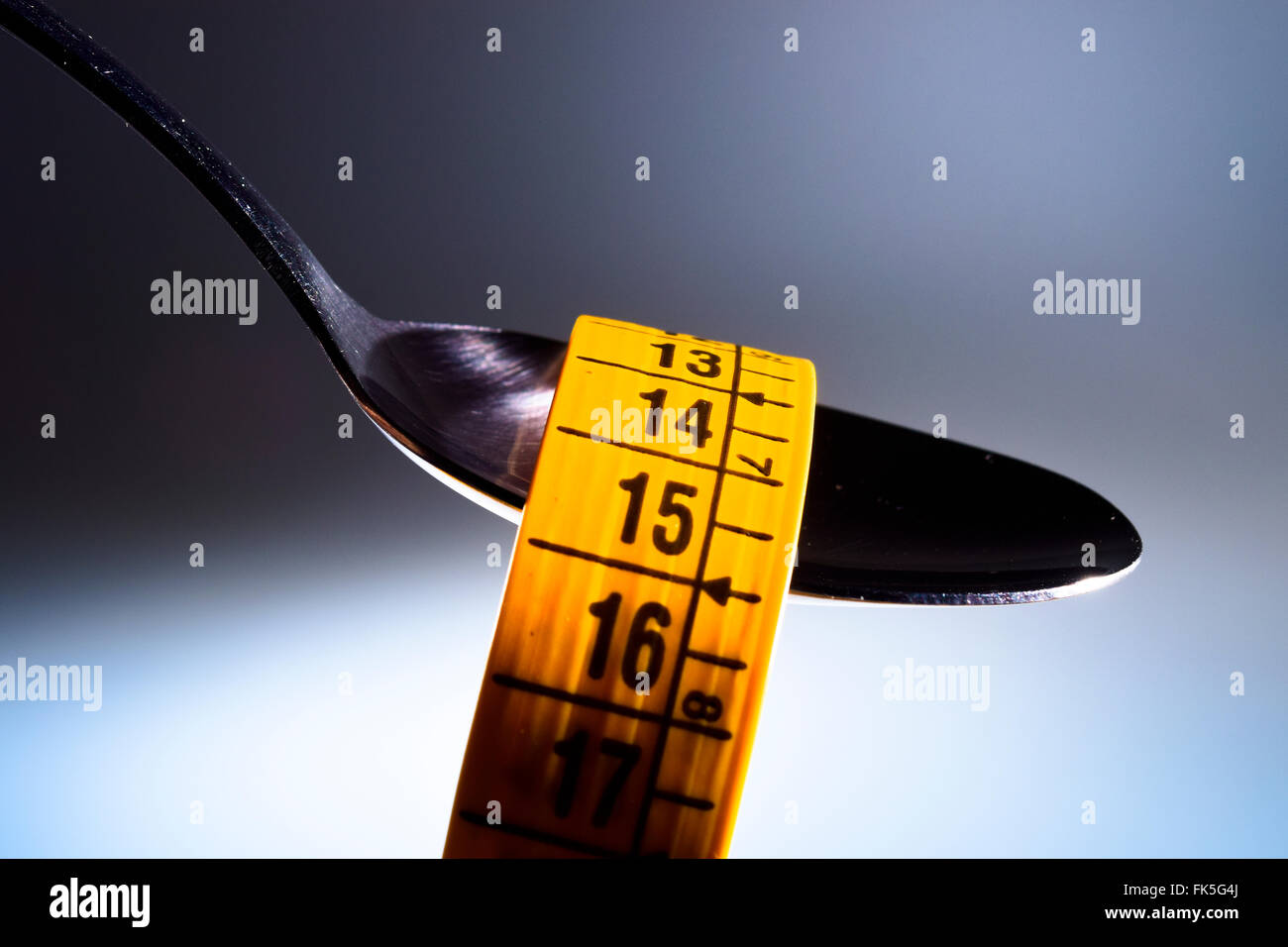 Spoon and measuring tape. Concept of nutrition and diet. - Stock Image