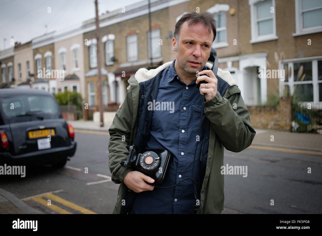 A man talks on an old style telephone in east London March 15, 2015. - Stock Image