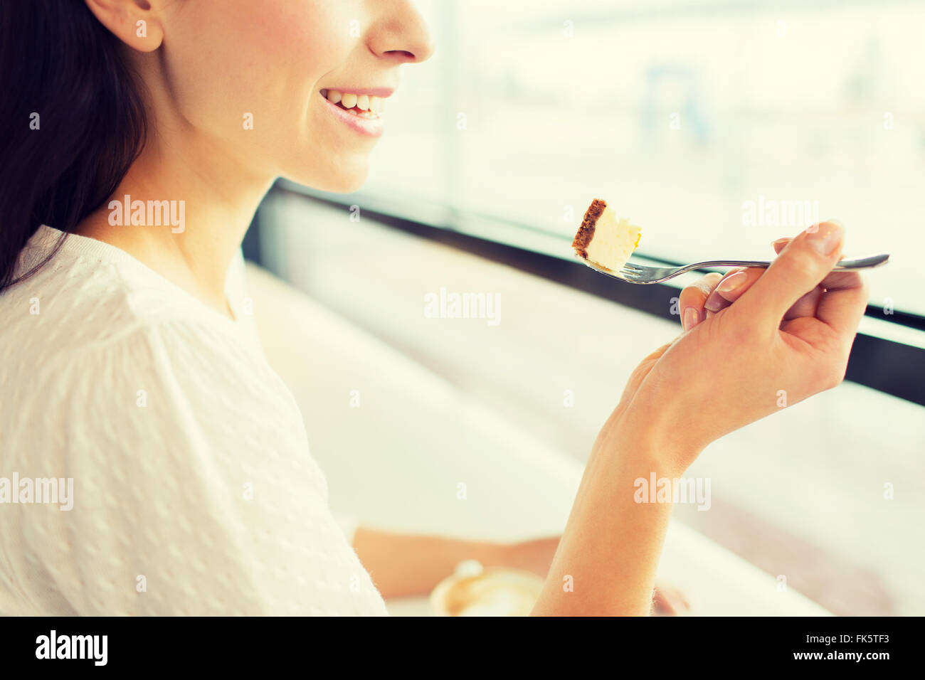close up of woman eating cake at cafe or home - Stock Image