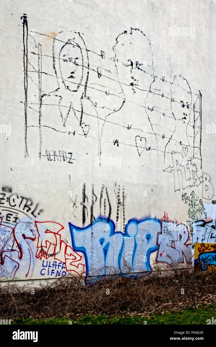 Topical street art, Refugees behind barb wire fence on building wall, Mitte, Berlin - Stock Image