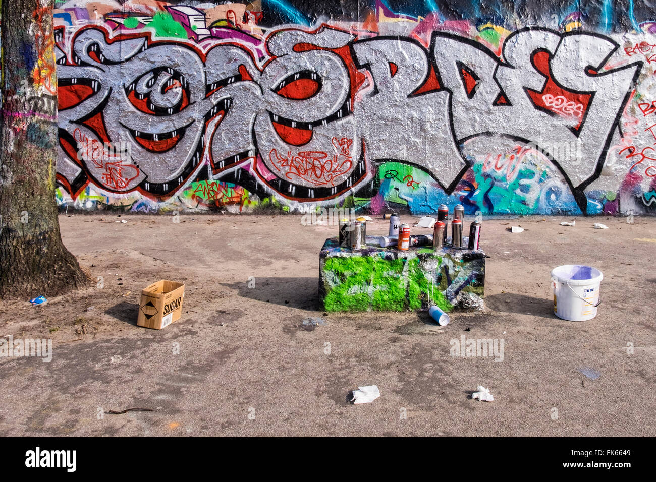 Graffiti on Berlin Wall and aerosol cans of spray paint left by street artists,Mauerpark, Berlin - Stock Image