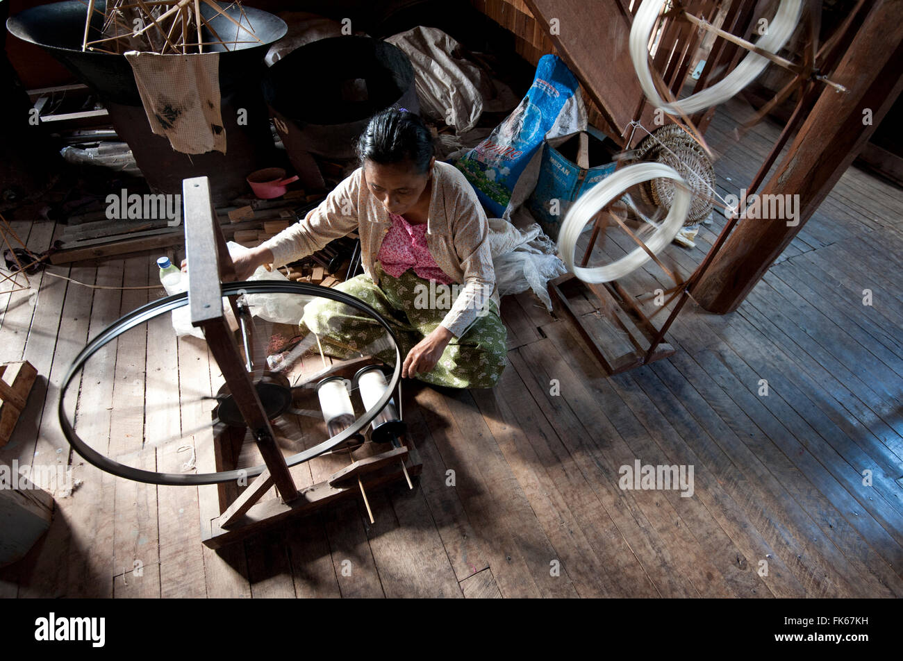 Woman spinning silk thread on a spinning wheel with bicycle wheel, Ko Than hlaing Weaving, Inpawkhan, Inle Lake, Stock Photo