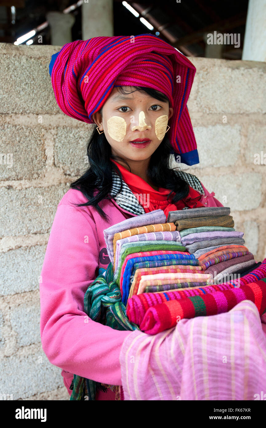 Young girl with thanaka paste on her face, selling scarves and sarongs at Nyaung Oak Monastery, Indein, Inle Lake, - Stock Image