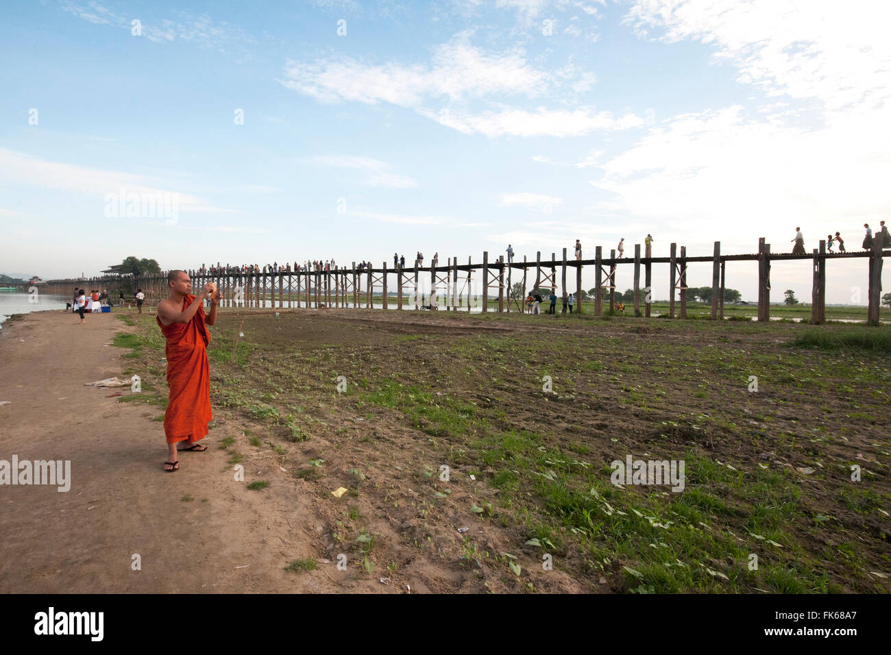 Orange robed monk photographing people crossing U Bein's Bridge, supported by 984 teak posts over Thaumthaman - Stock Image