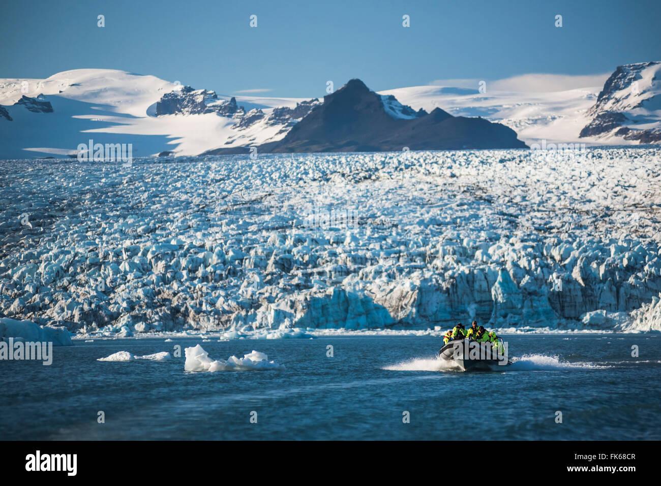 Zodiac boat tour on Jokulsarlon Glacier Lagoon, with Breidamerkurjokull Glacier and Vatnajokull Ice Cap behind, Stock Photo