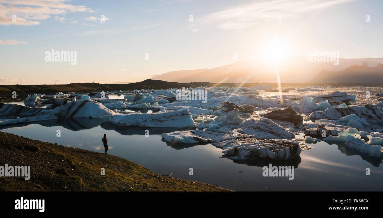 Tourist at Jokulsarlon Glacier Lagoon at sunset, South East Iceland, Iceland, Polar Regions Stock Photo