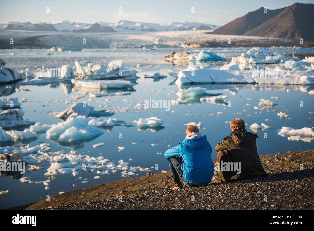 Father and son on holiday at Jokulsarlon Glacier Lagoon at sunset, South East Iceland, Iceland, Polar Regions Stock Photo