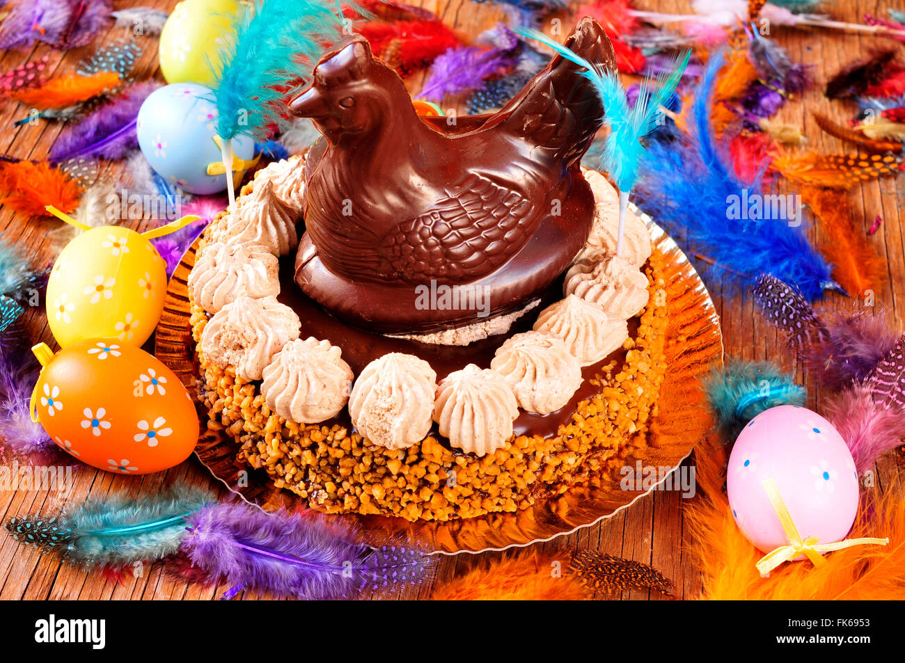 a mona de pascua, a cake eaten in Spain on Easter Monday, topped with a chocolate chicken, on a rustic wooden surface Stock Photo
