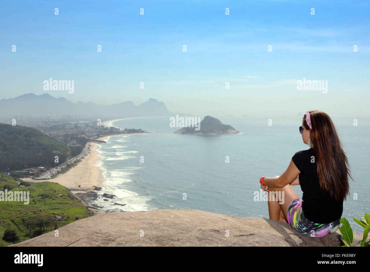 A hiker looking out from the viewpoint over Pontal and Recreio dos Bandeirantes beaches in Barra da Tijuca, Rio - Stock Image