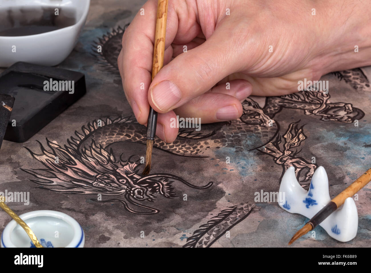 Artist using calligraphy brush and block ink to paint a traditional Chinese dragon - Stock Image