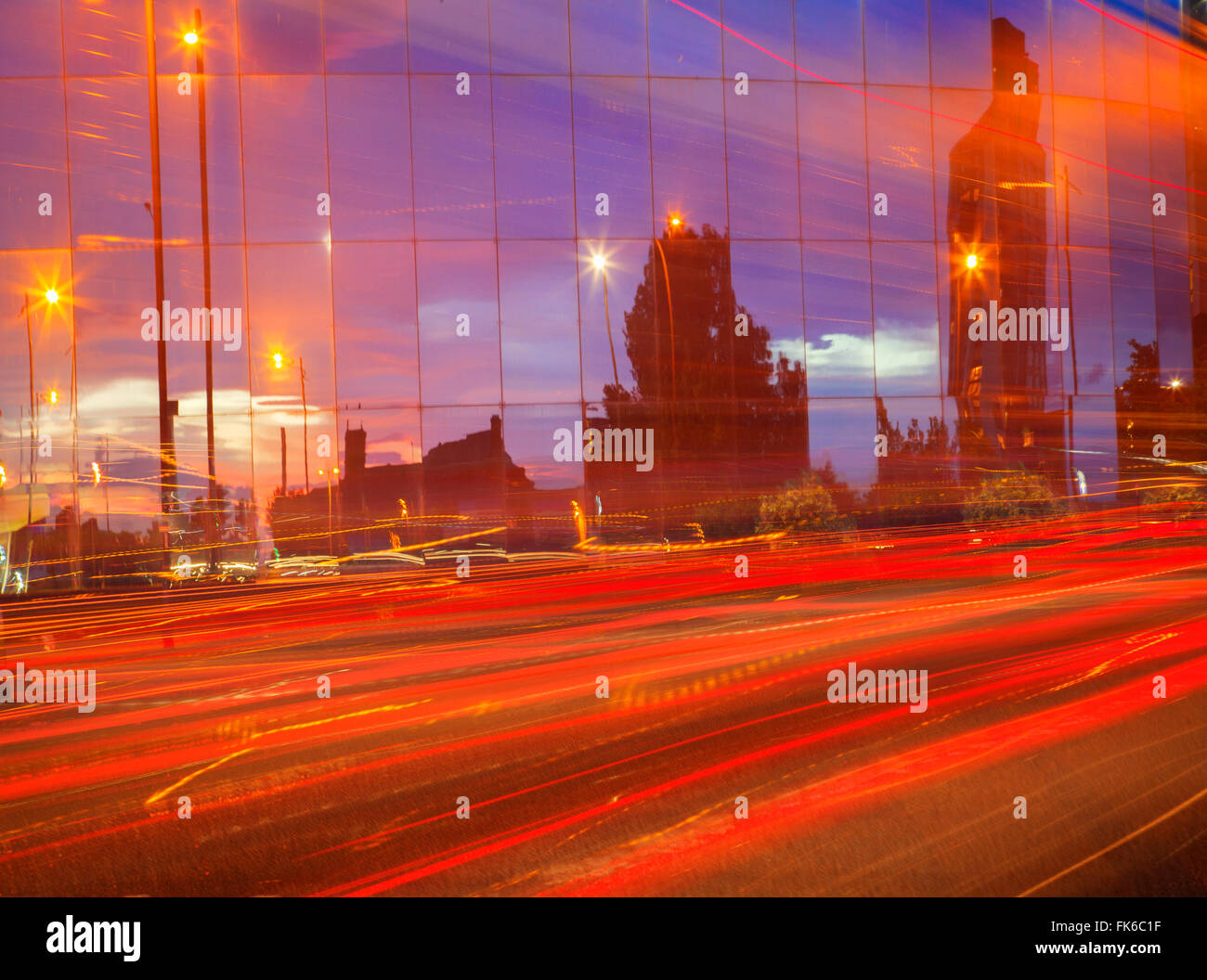 Car tail lights streaming past mirrored building, Liverpool, Merseyside, England, United Kingdom, Europe - Stock Image