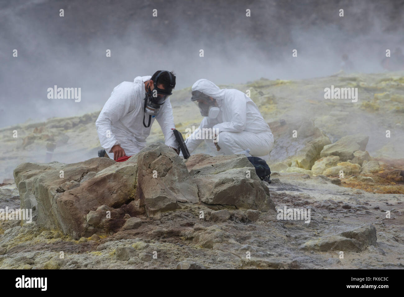 Geologists taking mineral samples on Gran Cratere, Vulcano Island, Aeolian Islands, UNESCO, Sicily, Italy - Stock Image