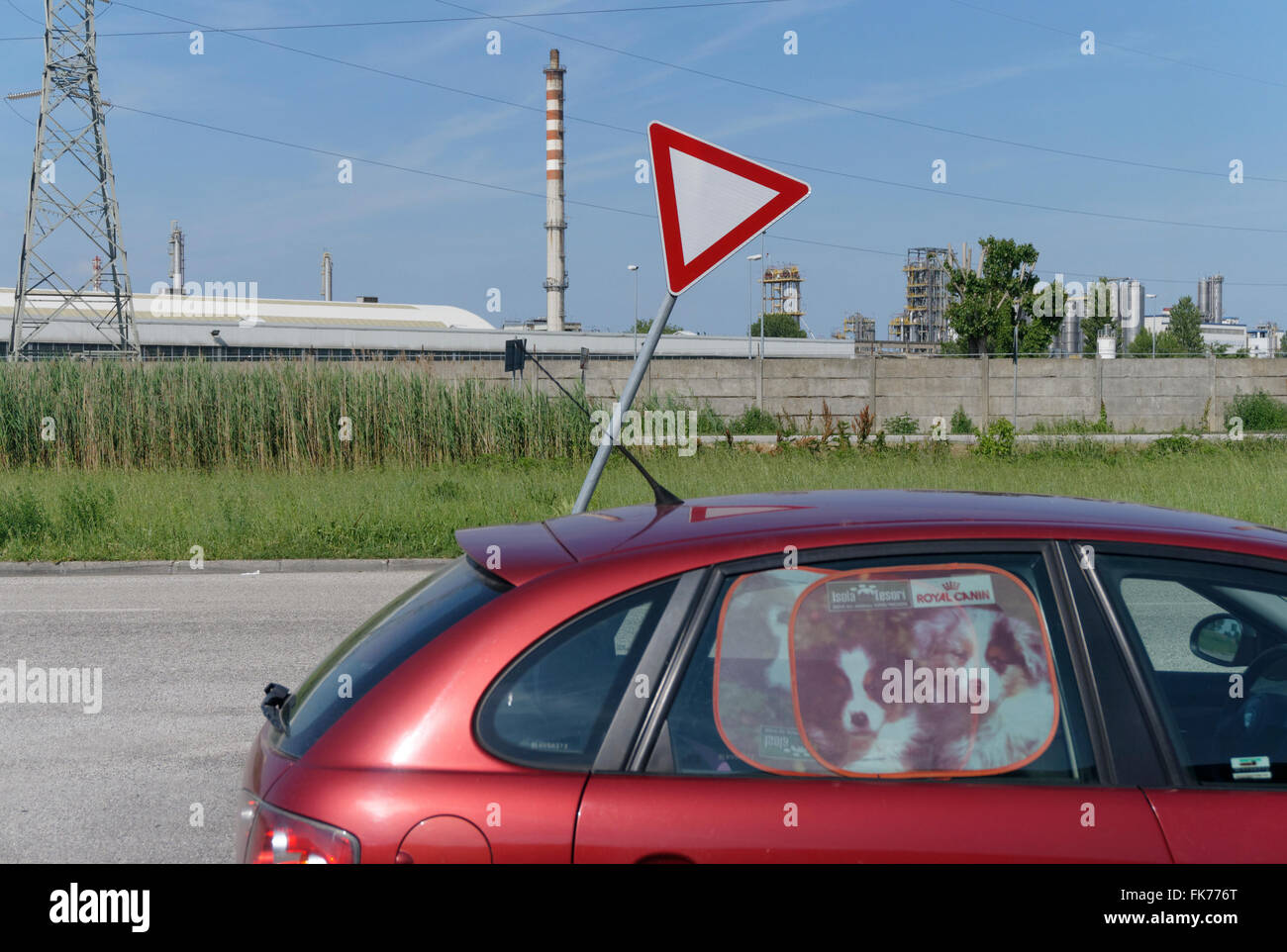 parked car, leaning road sign and a factory in the suburbs of Ferrara, Italy - Stock Image