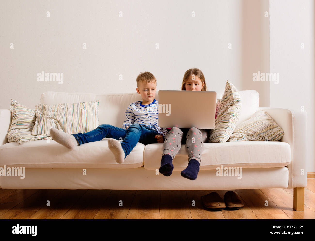 Children at home sitting on sofa, playing with laptop - Stock Image