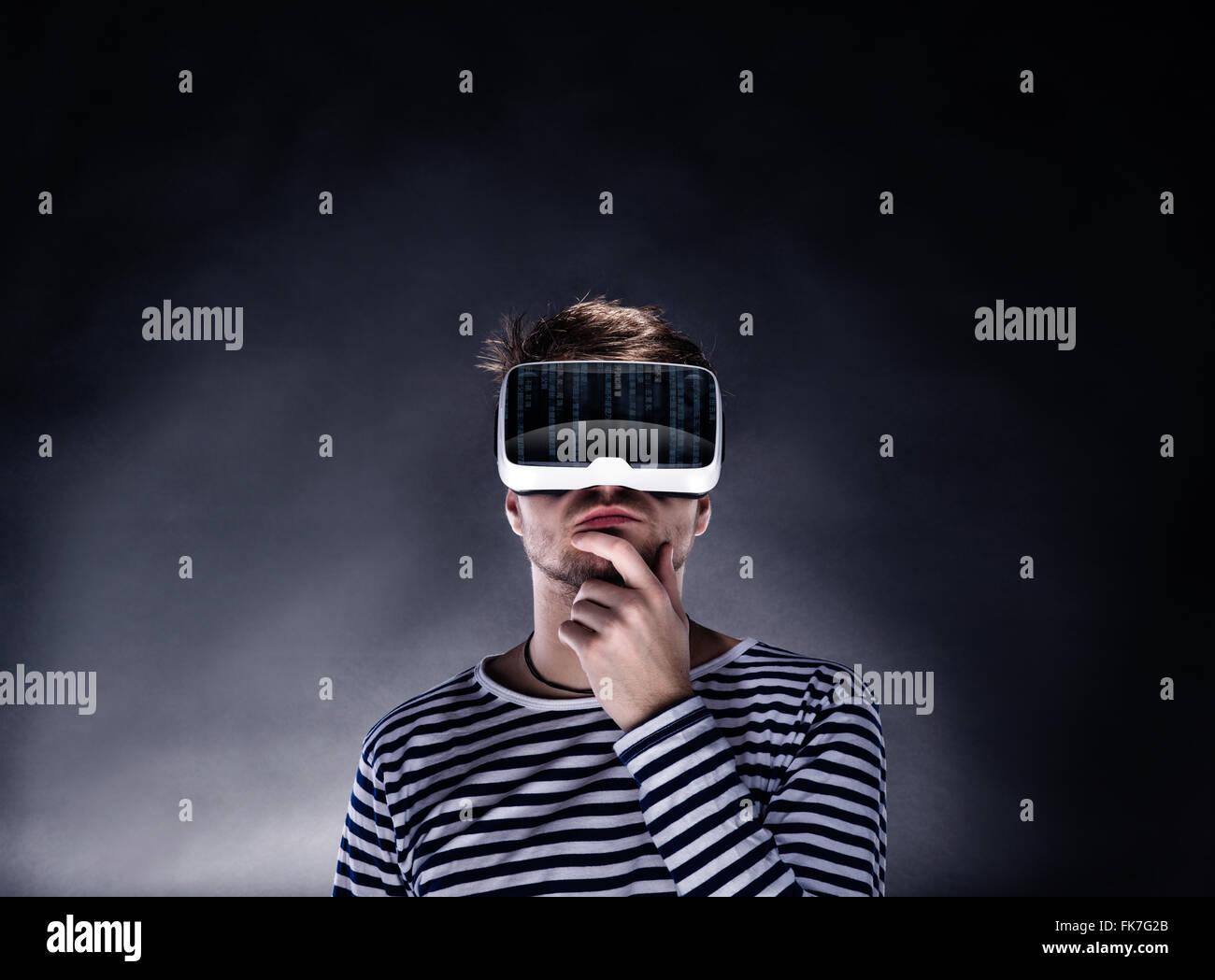 Man wearing virtual reality goggles. Studio shot, black backgrou - Stock Image