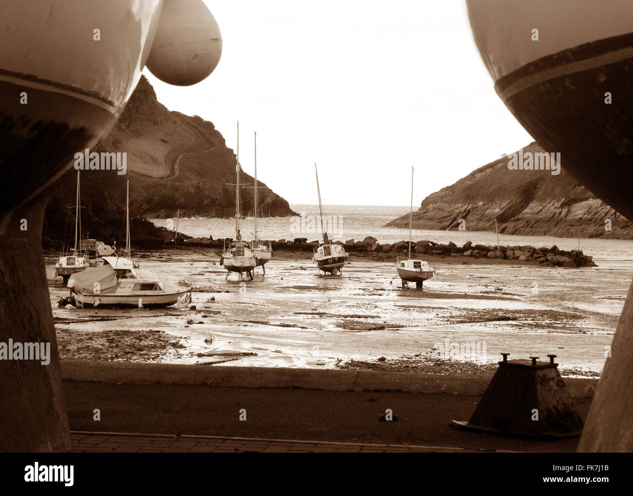 Watermouth Cove Near Ilfracombe Devon Tide out View from harbourside through hulls of boats Moody Picture - Stock Image