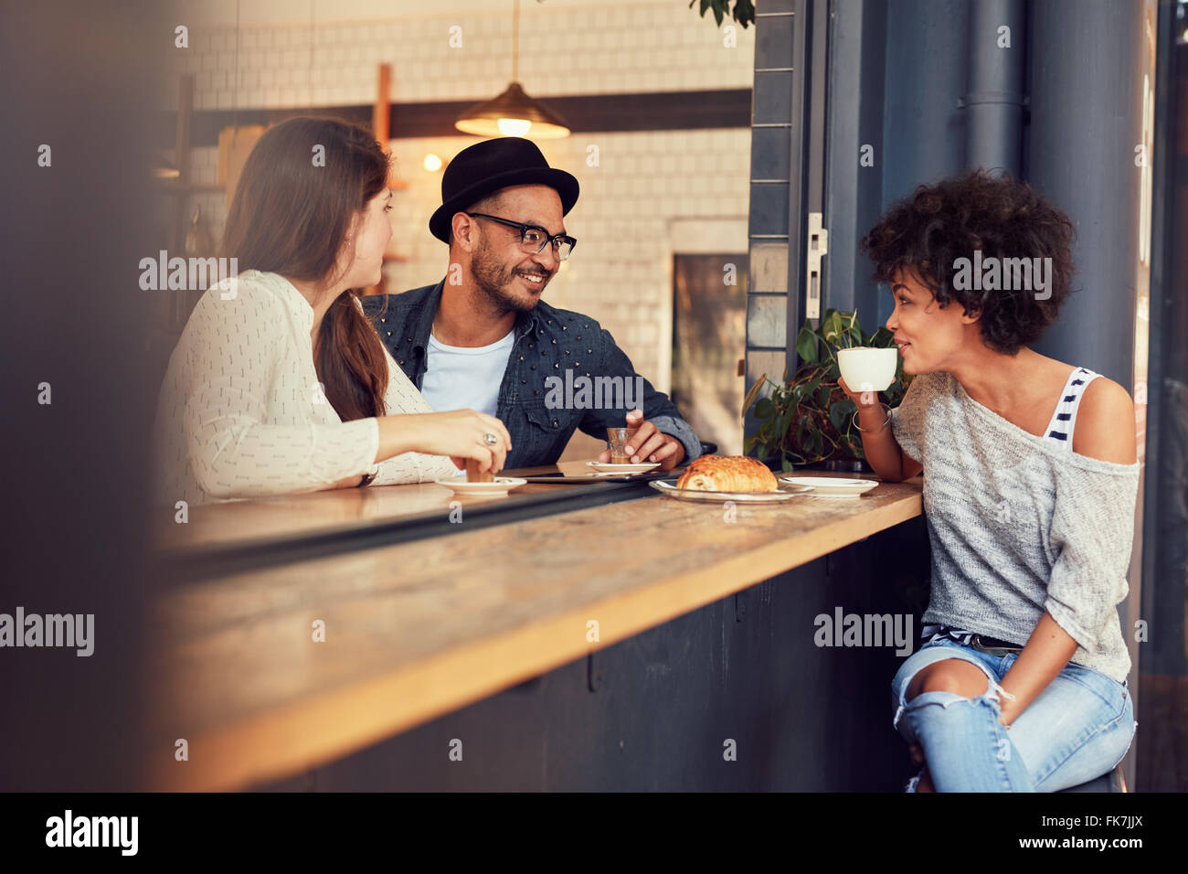 Happy young people sitting in a cafe and talking to each other. Group of young friends communicating and having Stock Photo