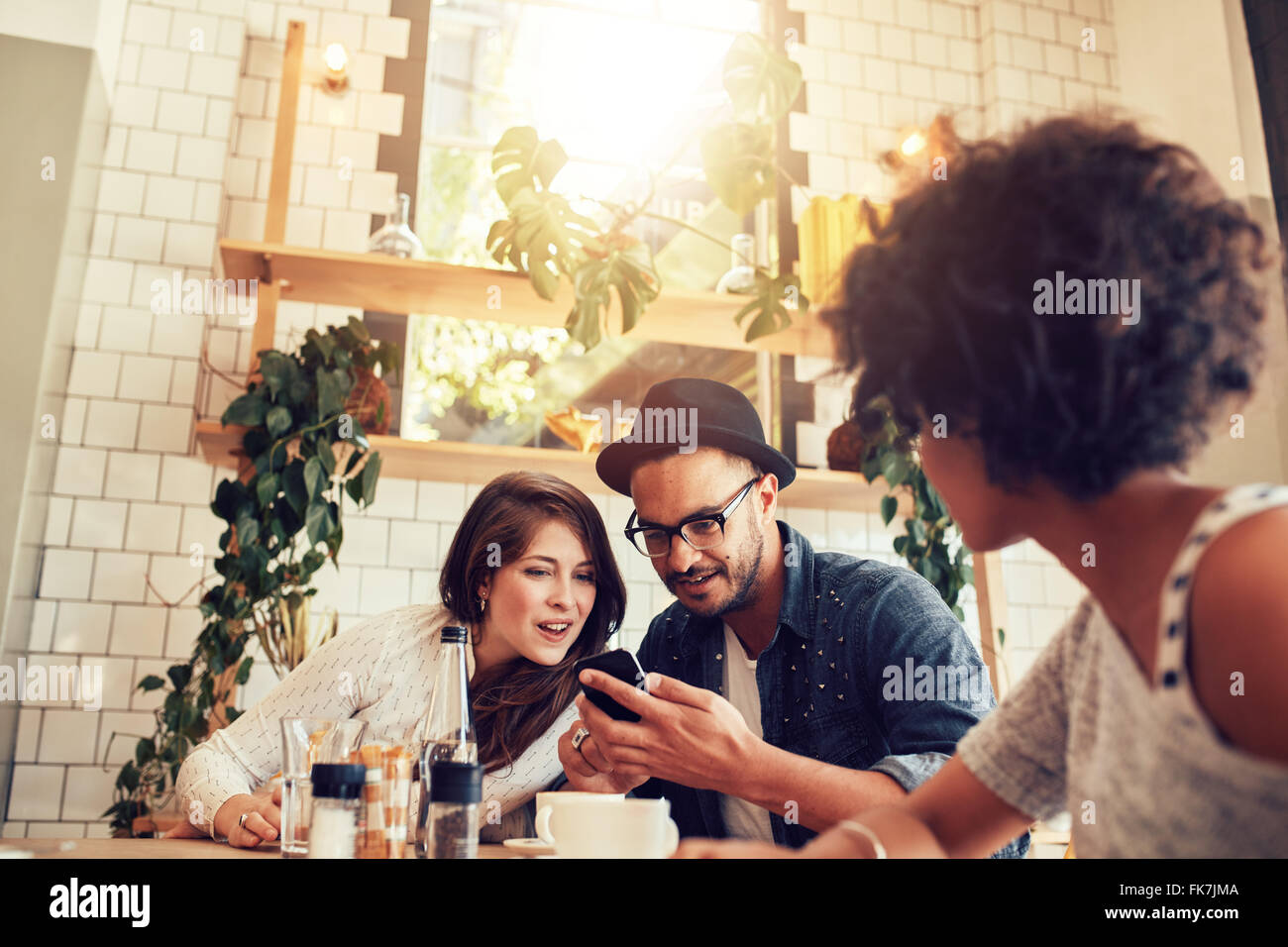 Young couple looking at smart phone while sitting in cafe with friends. Group of young people sitting at a table - Stock Image