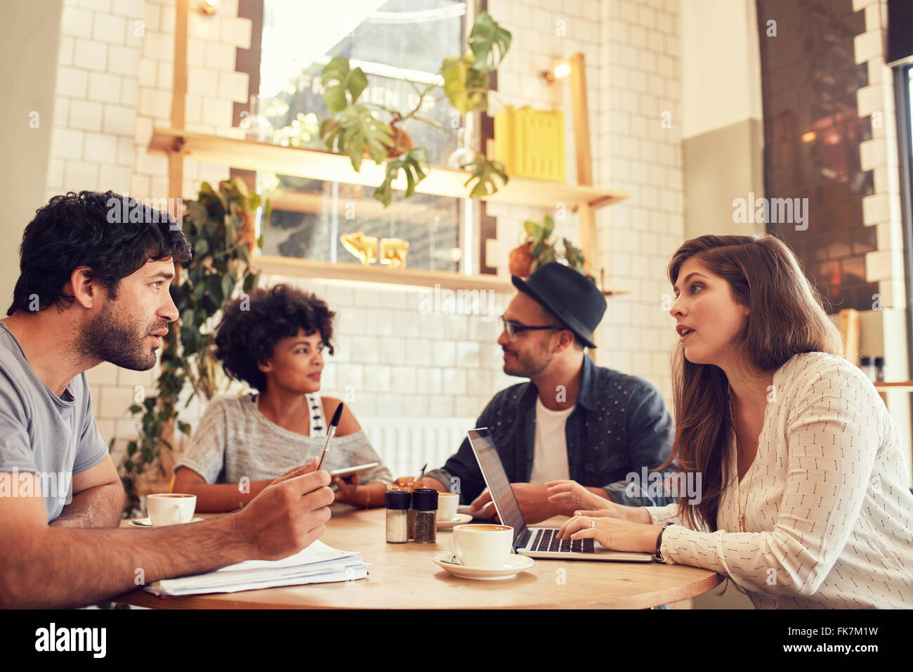 Portrait of young people sitting in a coffee shop with laptop and talking. Young men and women discussing business - Stock Image