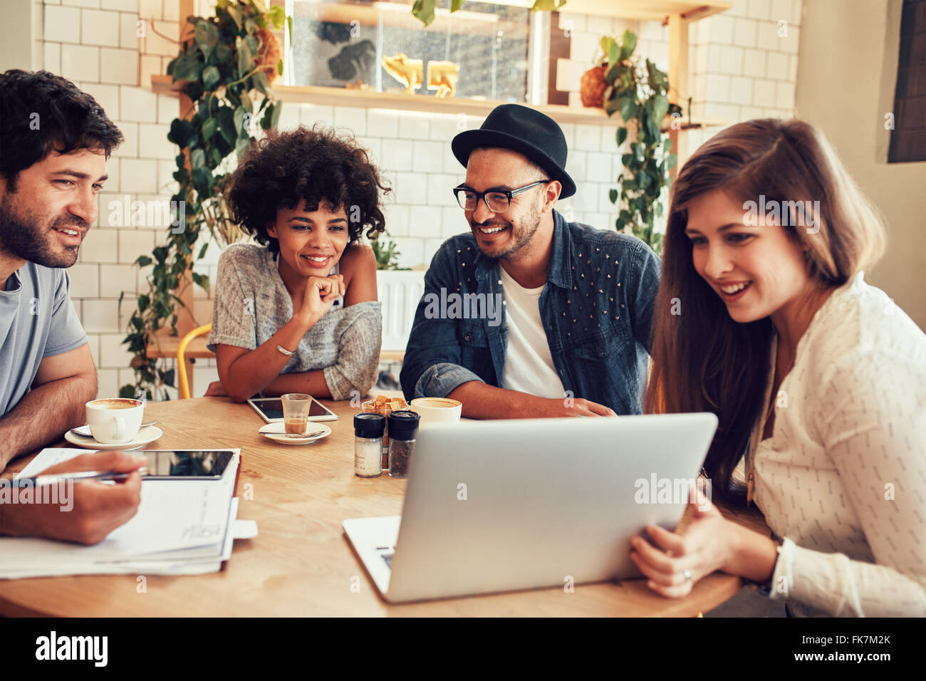 Group of friends hanging out in a coffee shop with a laptop amongst them. Happy young people sitting at restaurant - Stock Image