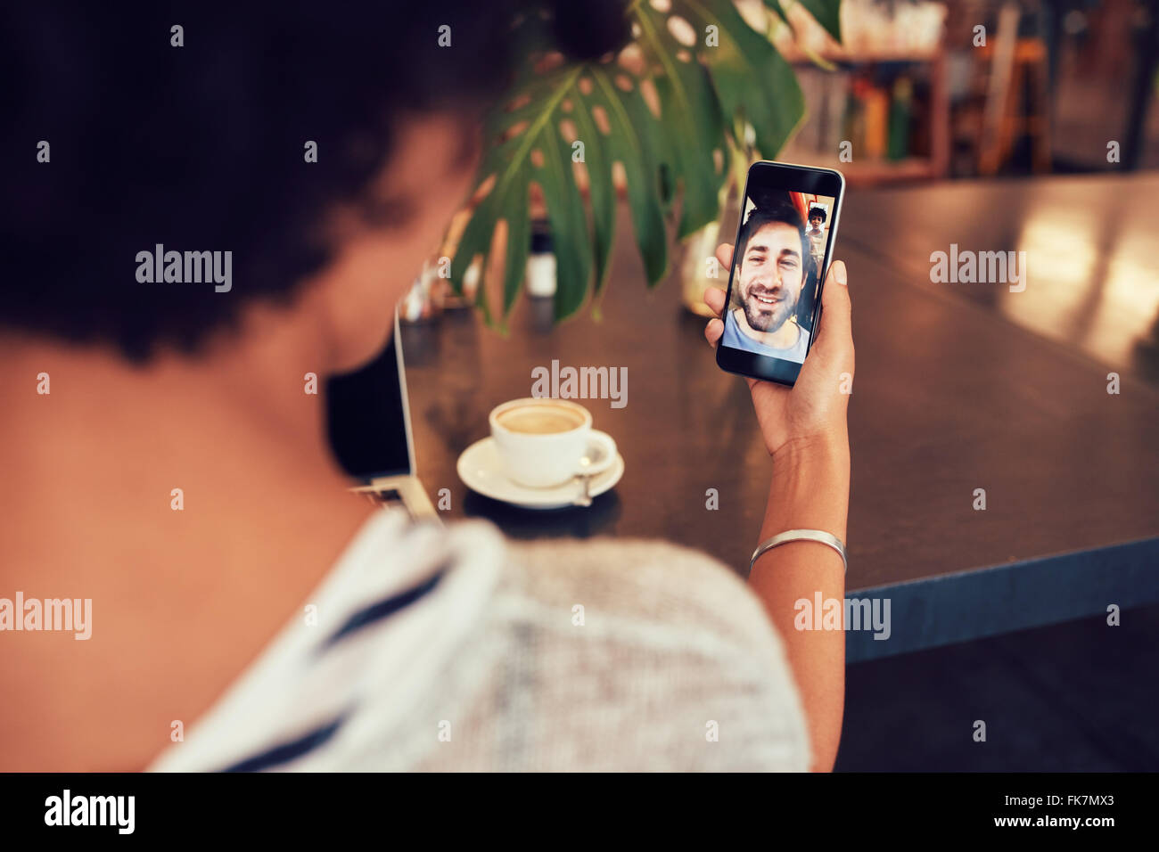 Young an and woman talking to each other through a video call on a smartphone. Young woman having a videochat with - Stock Image