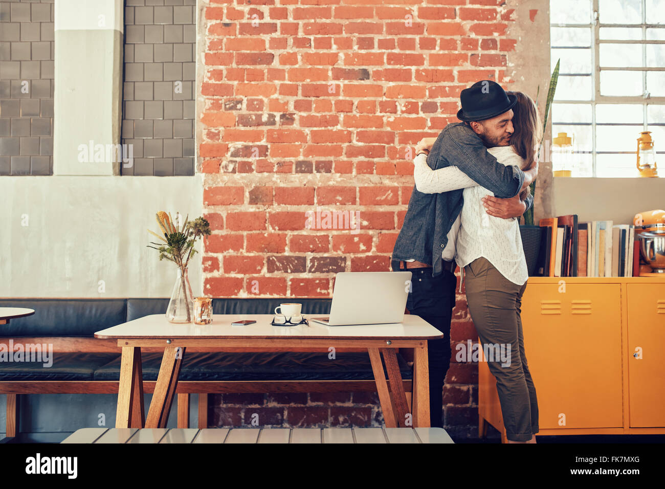 Portrait of man and woman hugging and greeting each other at a coffee shop, couple meeting in a cafe. - Stock Image