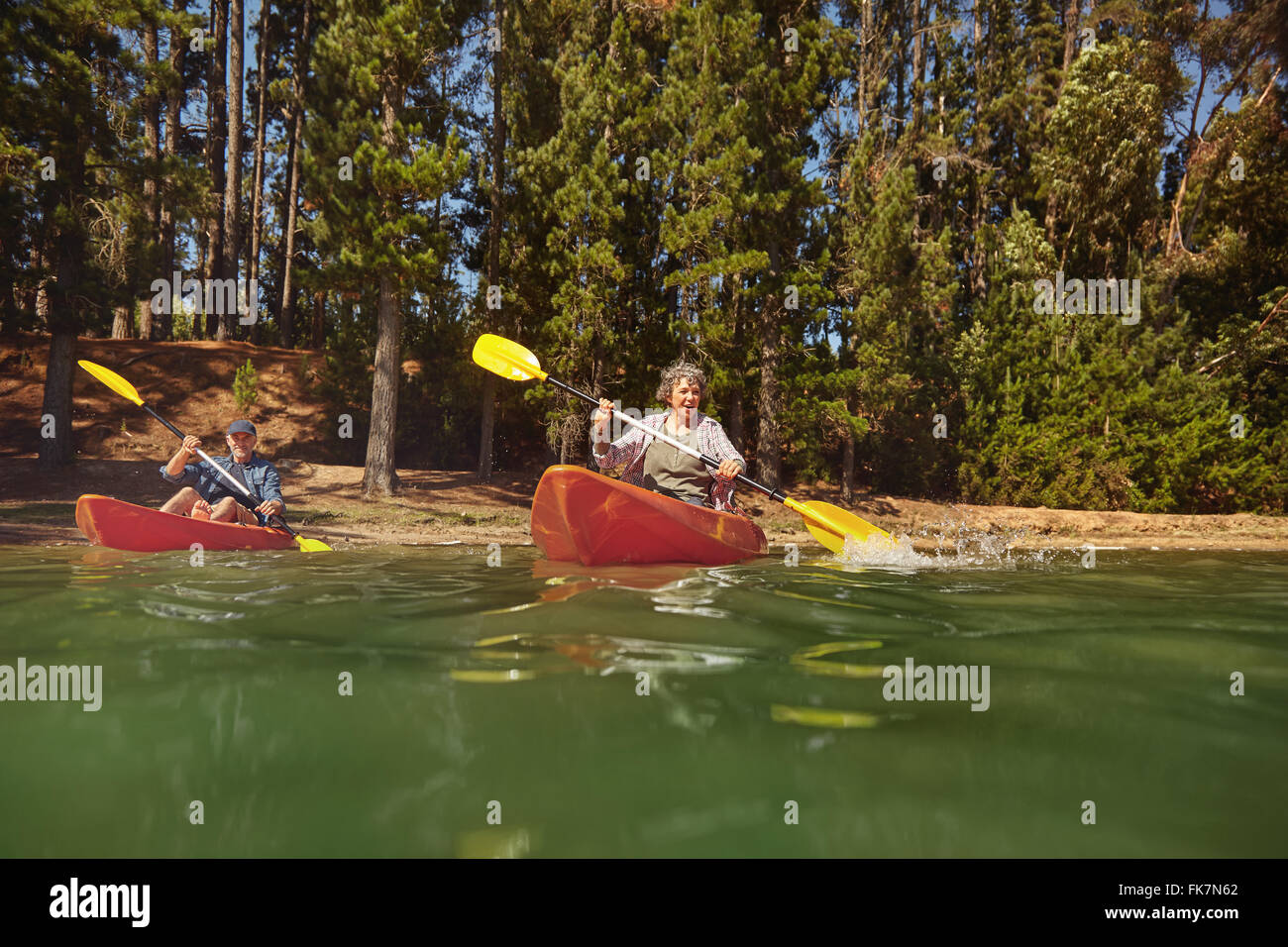 Portrait of a mature couple canoeing on a lake during a camping trip. Active senior couple in two single kayaks - Stock Image
