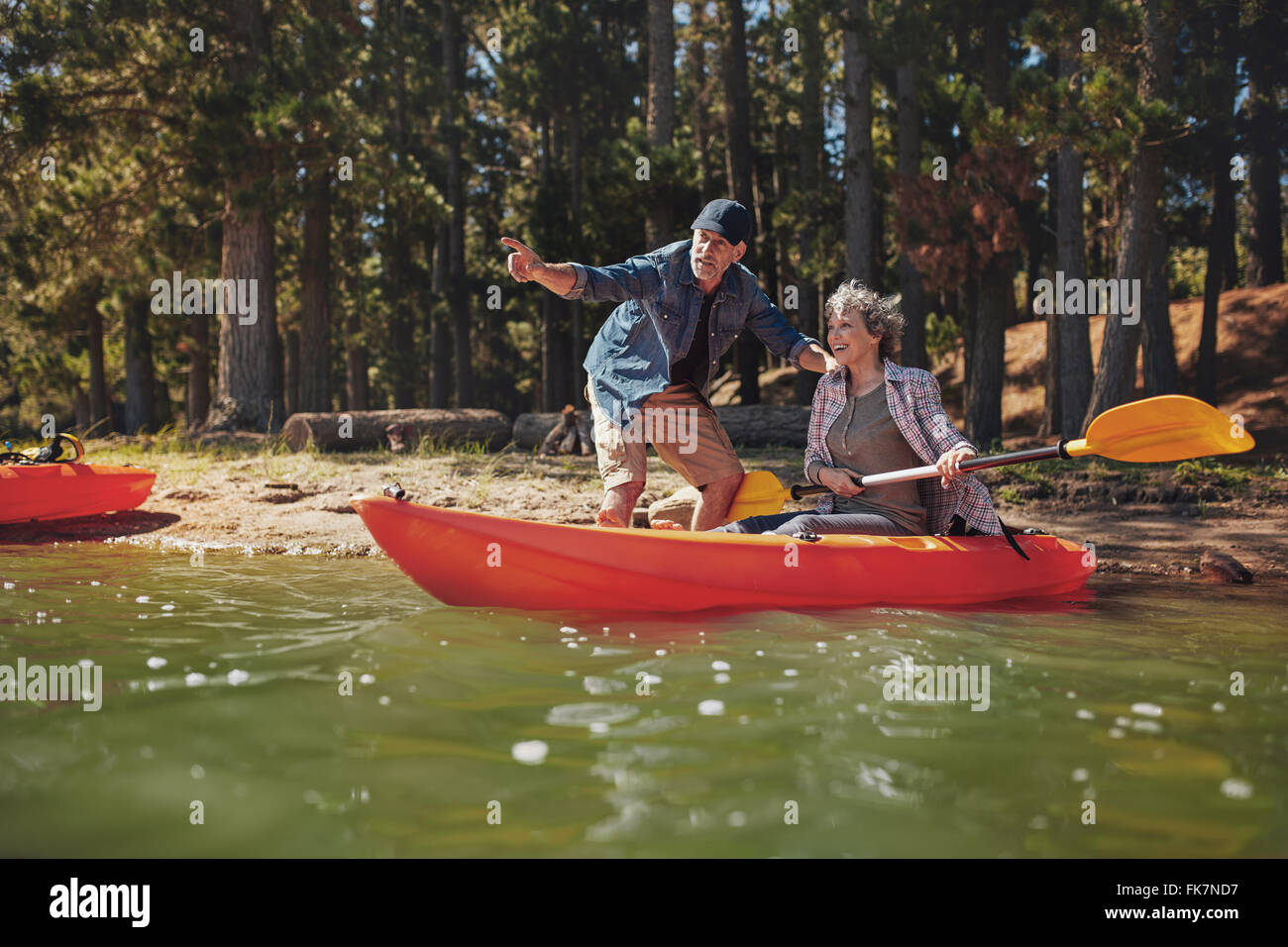 Portrait of mature man with a woman in a kayak in the lake. man showing something interesting to woman holding paddles. - Stock Image