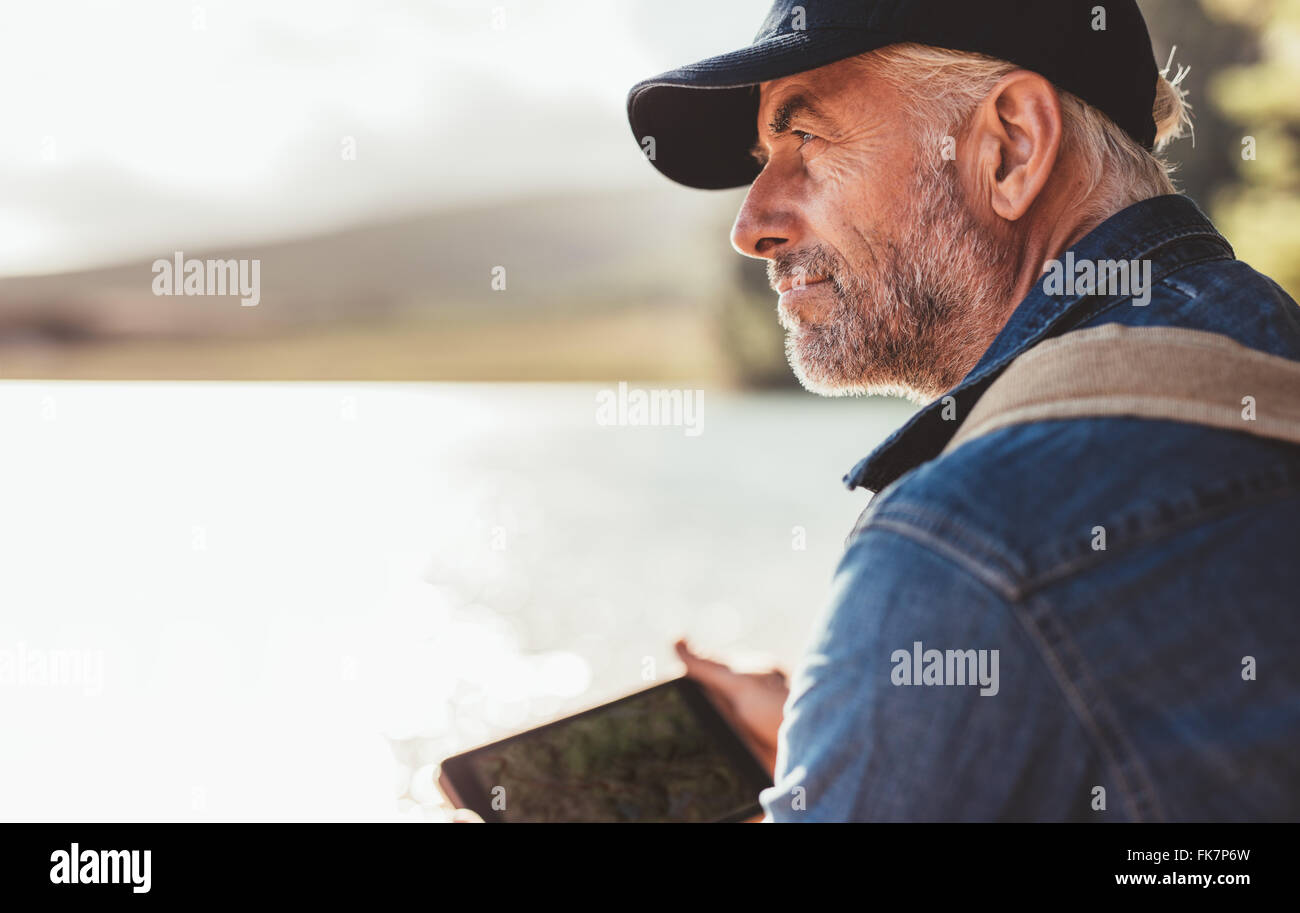 Close up portrait of mature man wearing cap sitting at a lake and looking at a view. Senior caucasian man with beard. - Stock Image