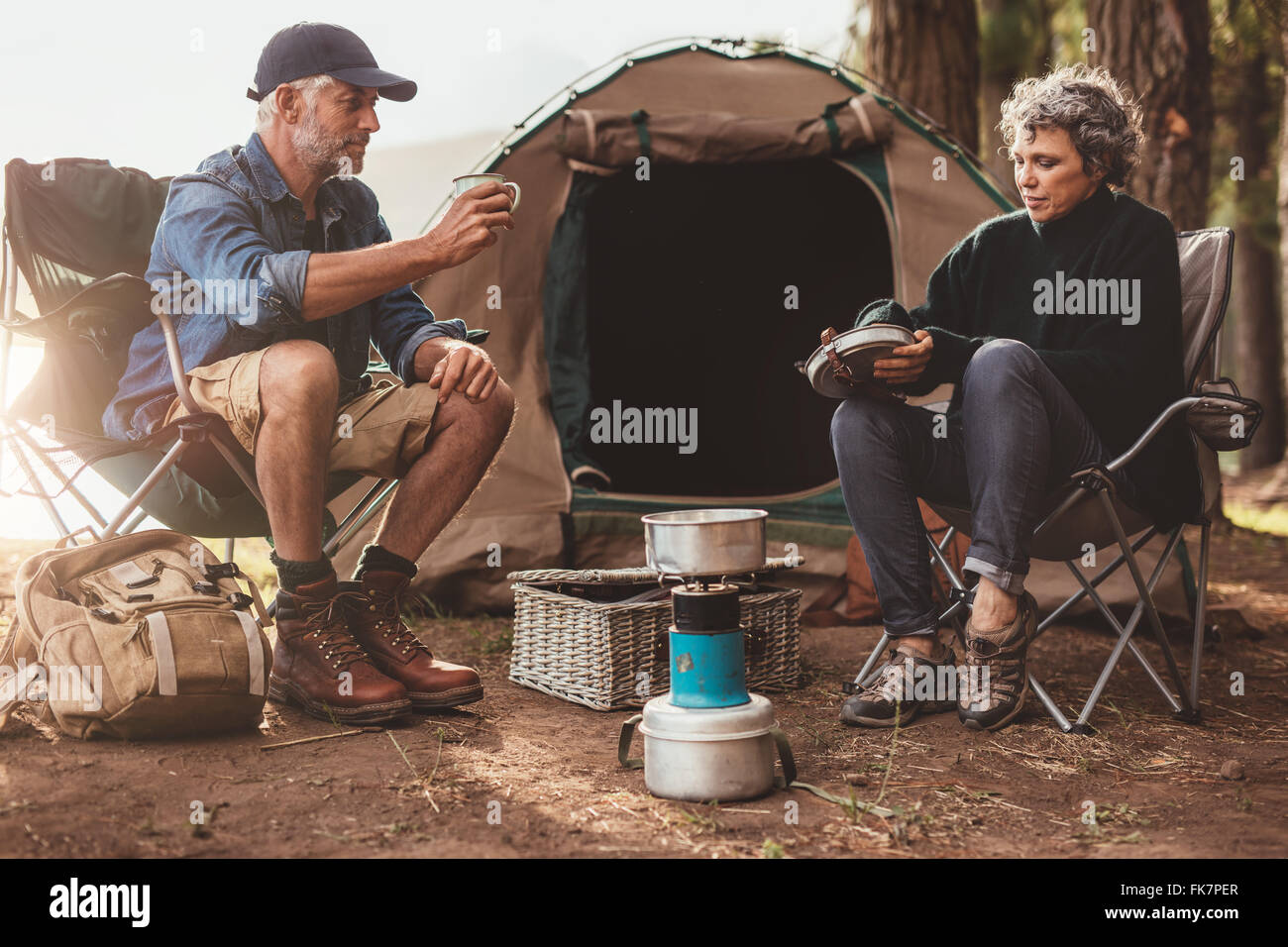 Couple sitting at their campsite, with man drink coffee. Senior couple camping in nature. - Stock Image