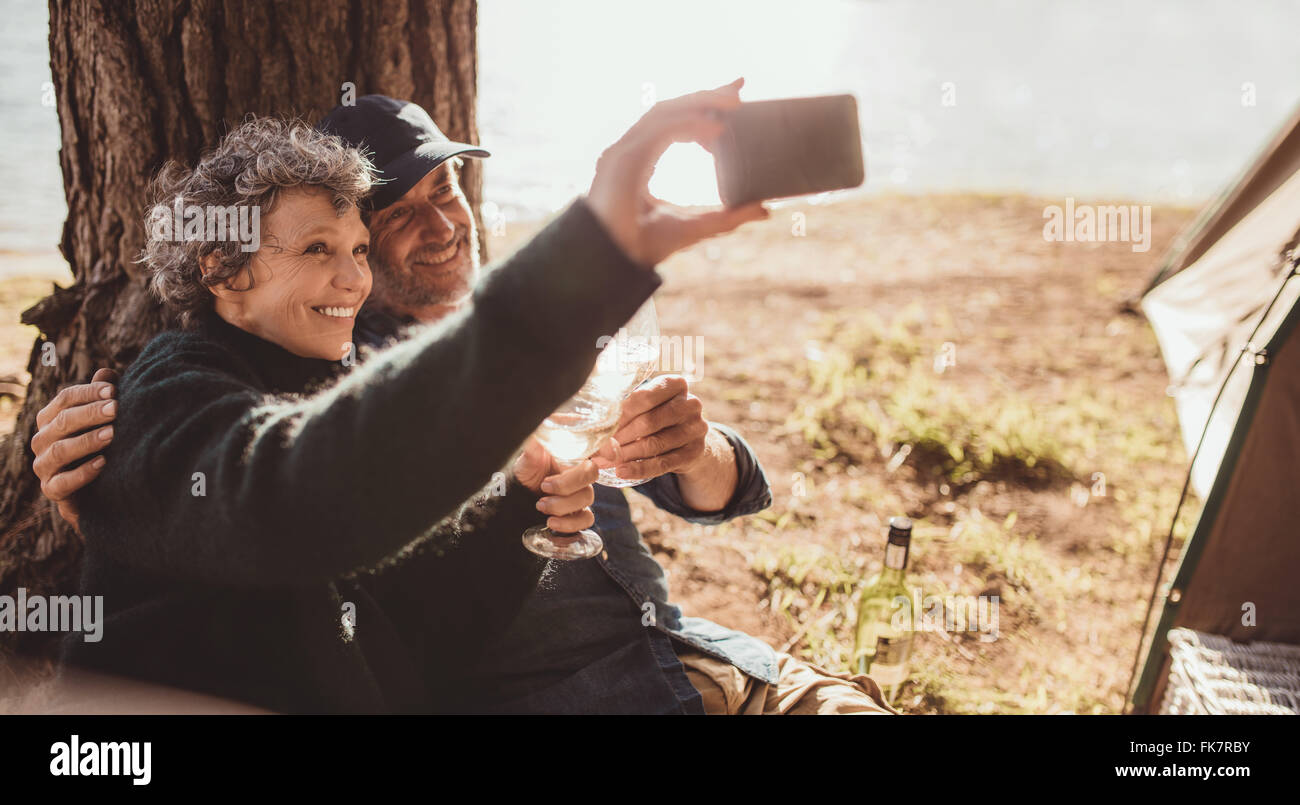 Senior man and woman sitting outdoors with a glass of wine taking a selfie with the mobile phone on camping trip. - Stock Image
