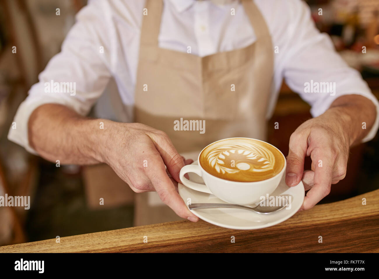 Close-up of man in apron serving coffee while standing in coffee shop. Barista giving you a cup of fresh coffee - Stock Image