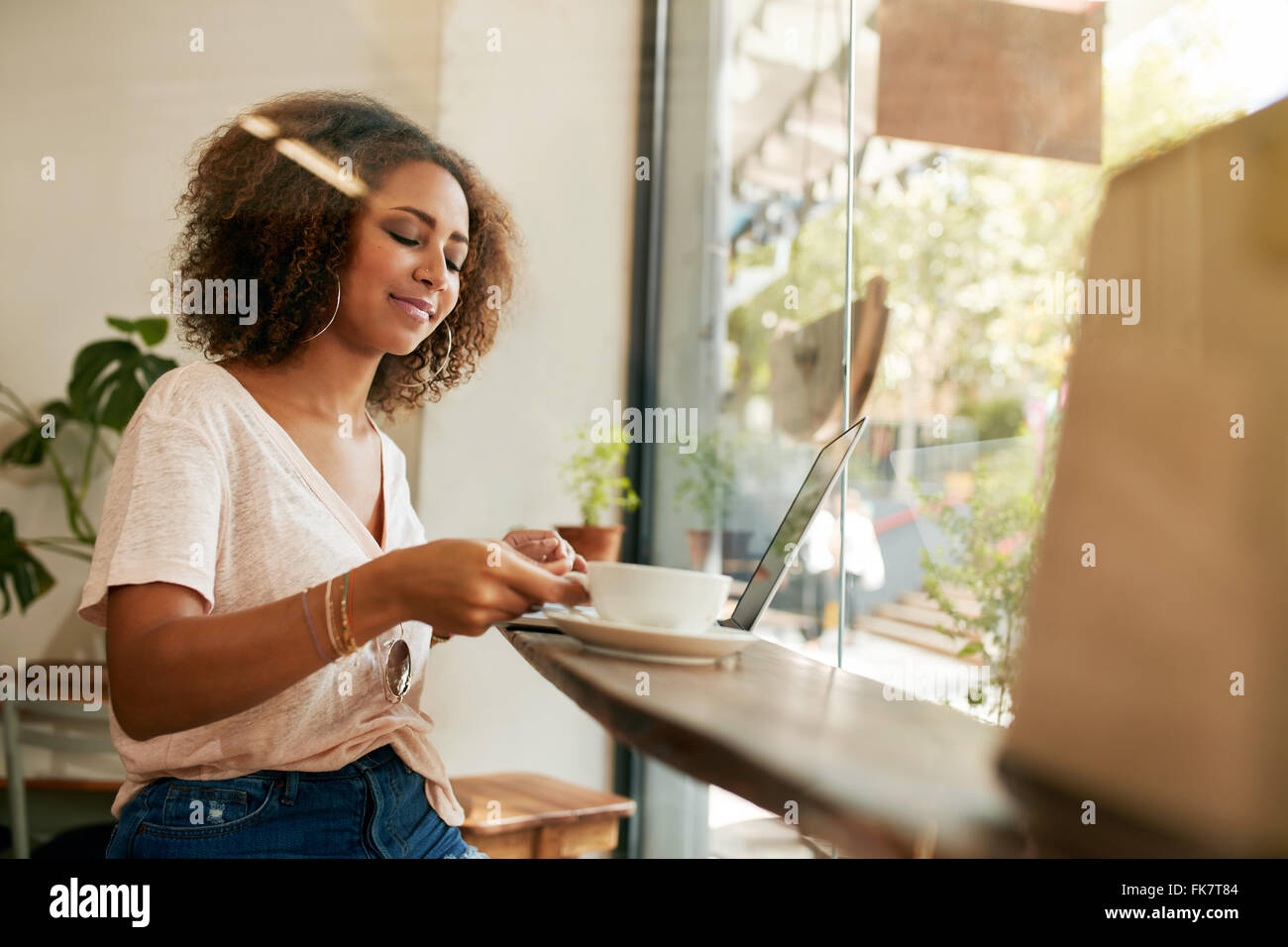 Shot of young african woman sitting in a cafe and drinking coffee. African female with laptop having coffee at restaurant. - Stock Image