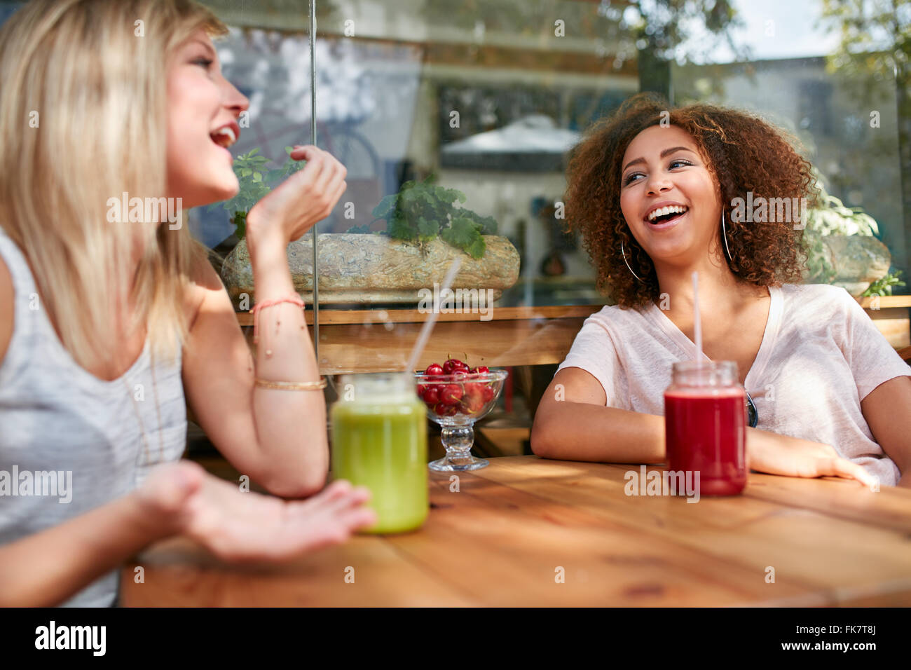 Two women gossiping and smiling at a restaurant. Young friends sitting at outdoors cafe having fun. - Stock Image