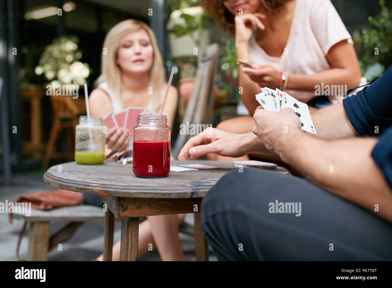 Cropped shot of young friends sitting at outdoor cafe playing card game. Players holding the cards while sitting - Stock Image