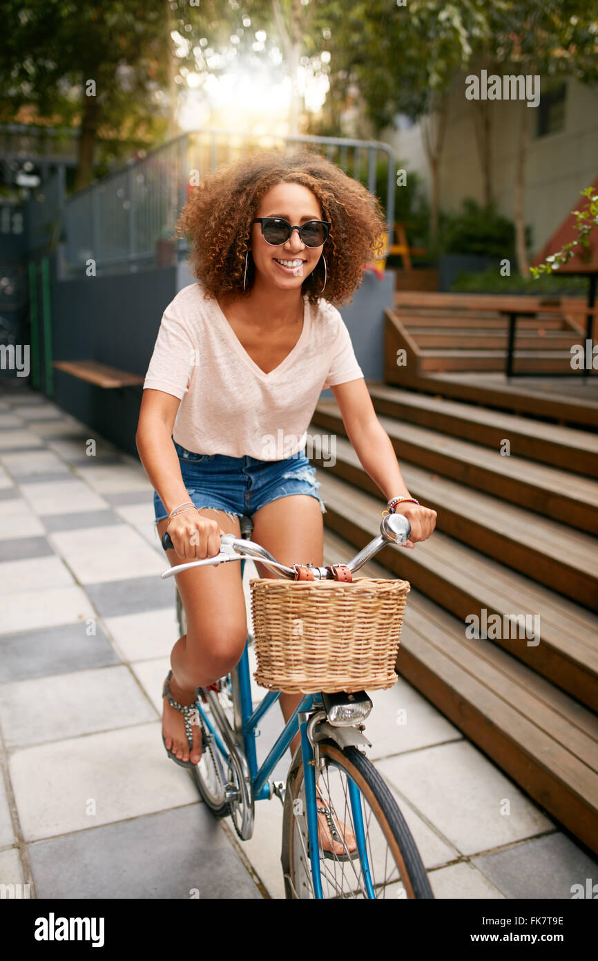Shot of a beautiful young woman riding her bike on sidewalk. African young girl wearing sunglasses enjoying bicycle - Stock Image