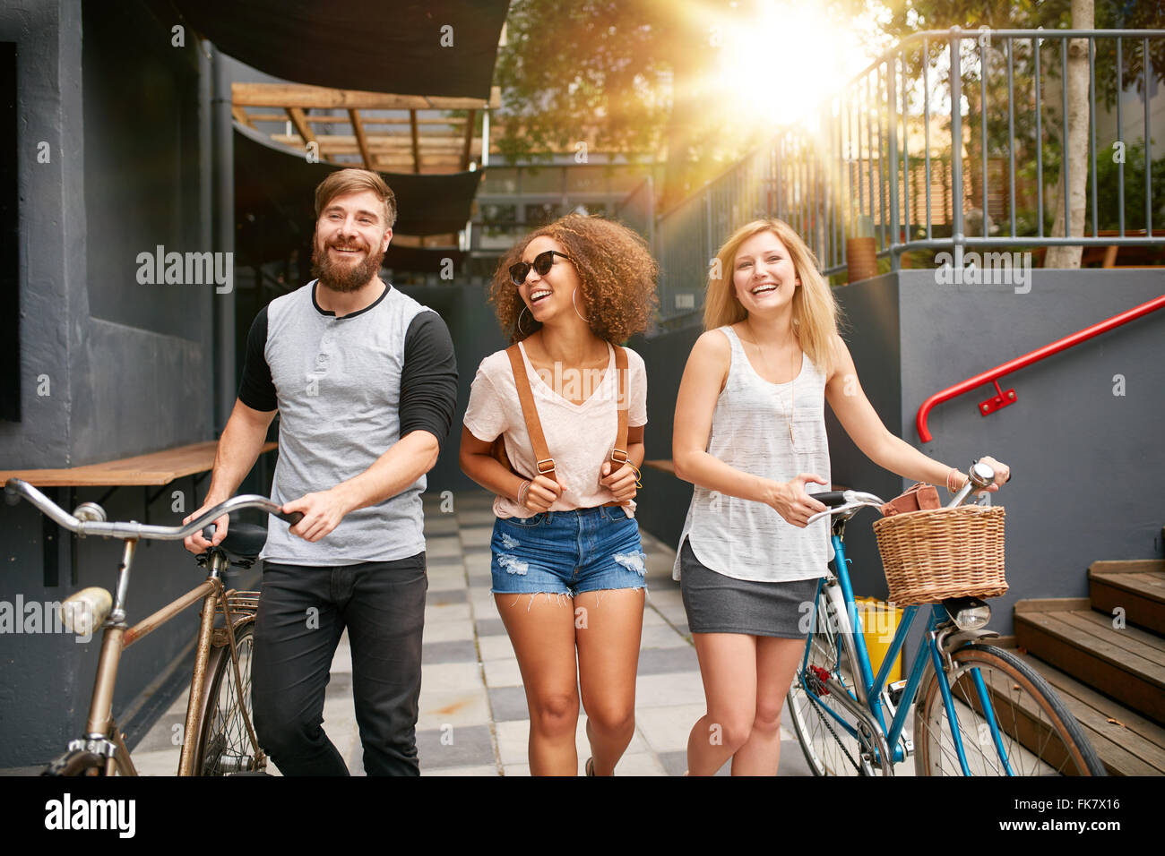 Three young adults walking together having fun. Young people with bikes walking outdoors in city. - Stock Image