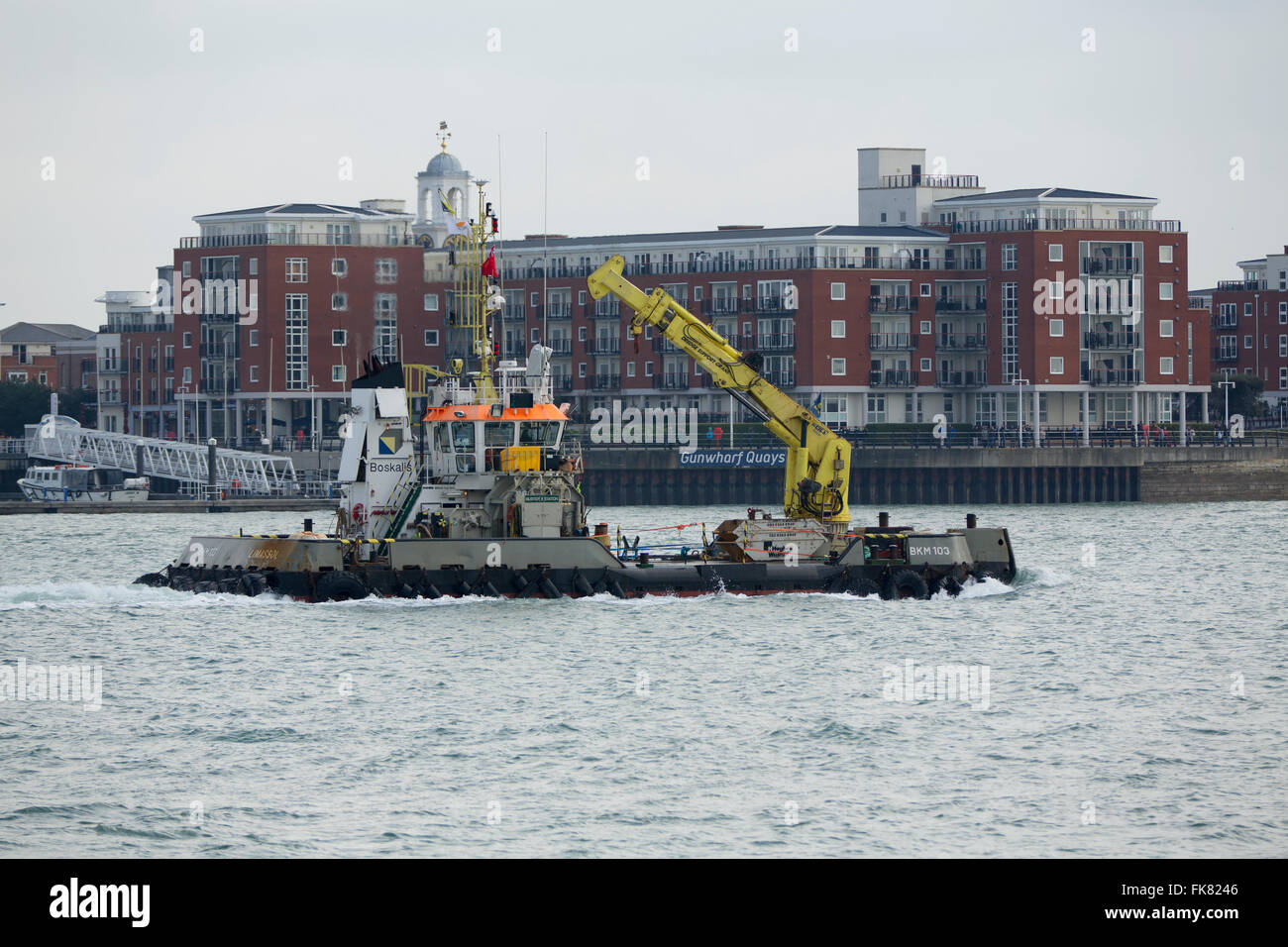 Dredger passing in front of Gunwharf Quays in Portsmouth. - Stock Image