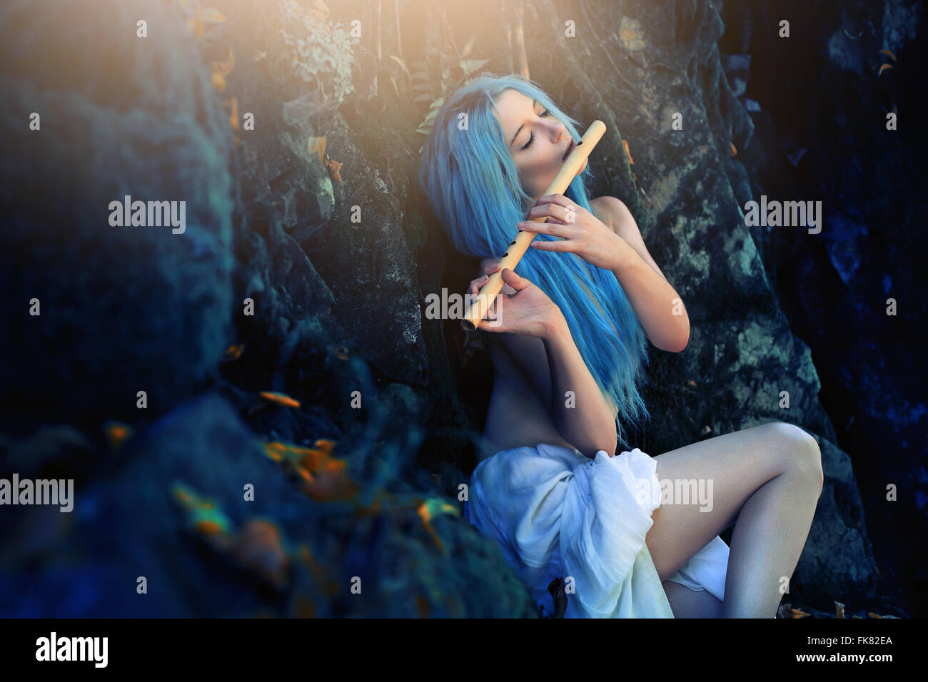 Beautiful ethereal creature of the forest playing flute . Fantasy and surreal - Stock Image