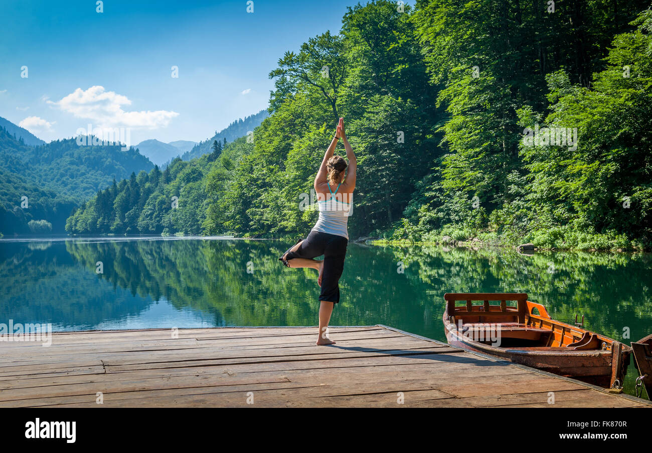 Yoga exercises at mountain forest lake. - Stock Image