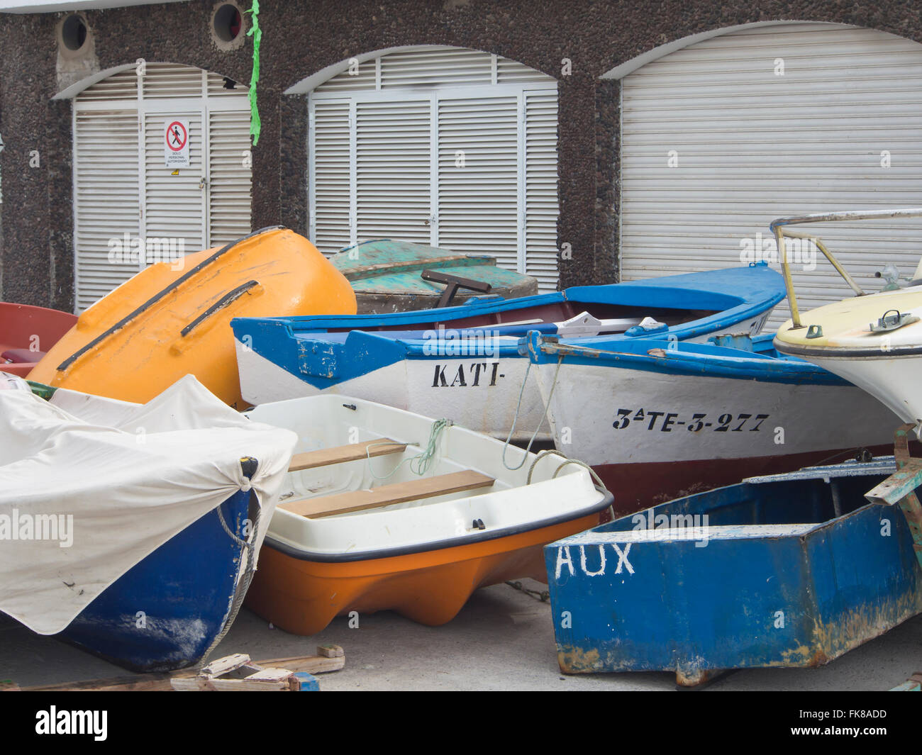 Cluster of traditional small fishing boats in front of a row of boathouse doors, Alcala Tenerife Canary Islands - Stock Image