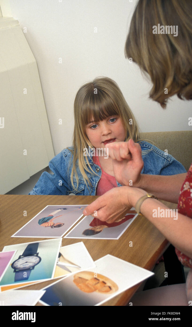 Speech therapist and young girl in therapy room using sign language - Stock Image
