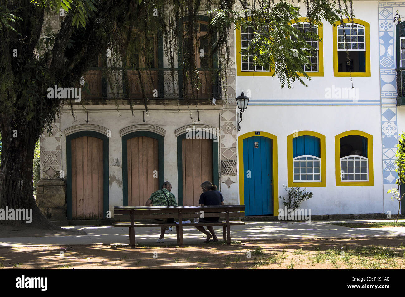 People sitting on the park bench Matrix and colonial houses in historic center - Stock Image