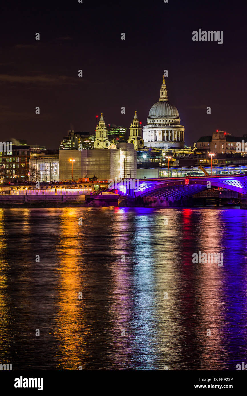 St Paul's cathedral over Blackfriars Bridge and Thames river at night with lights reflecting in the water. - Stock Image
