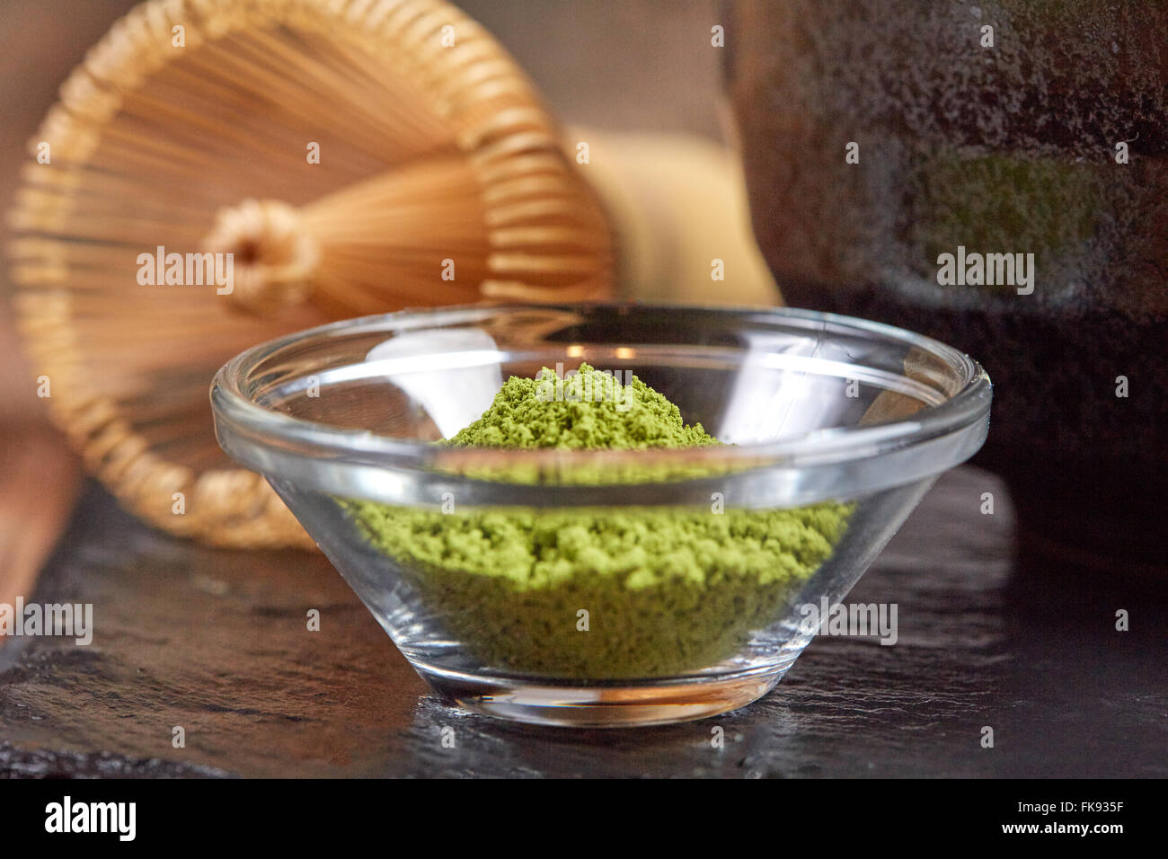 Green matcha tea and whisk on black stone plate on a wooden table - Stock Image