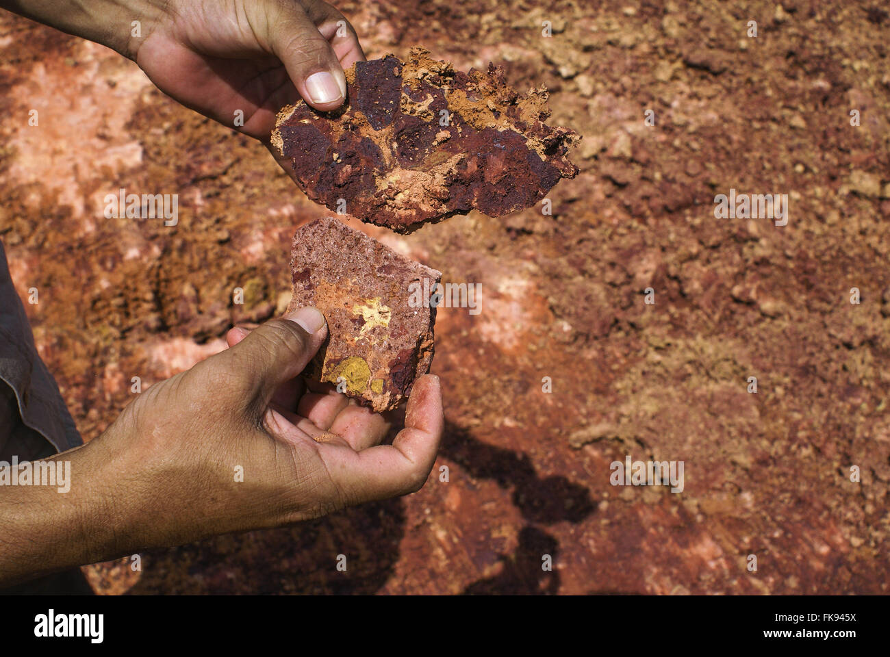 Comparison between that and bauxite or not - bauxite and the more reddish stone in left hand - Stock Image