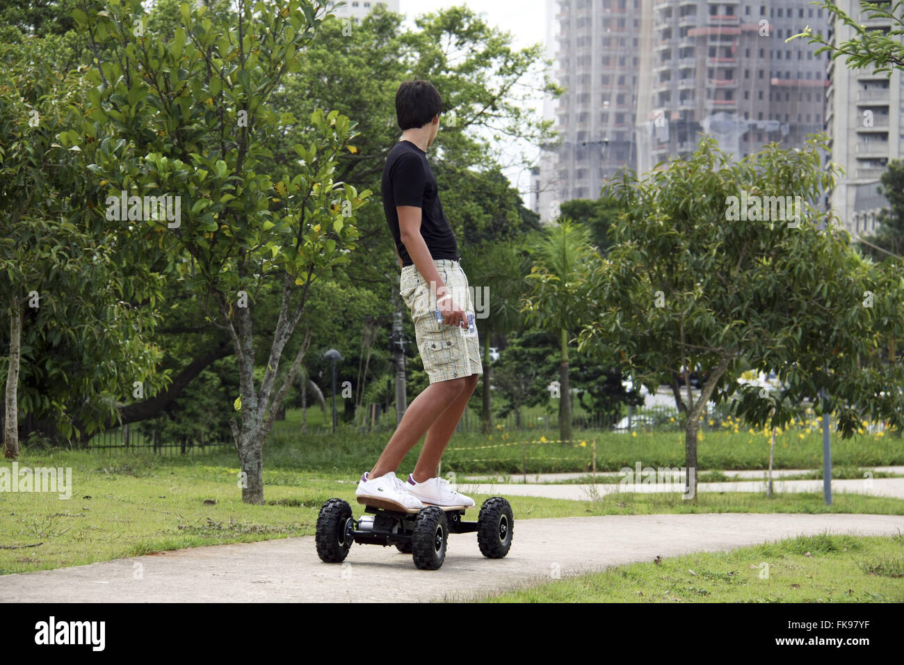 Young with motorized skateboard in People`s Park in Itaim Bibi neighborhood - Stock Image