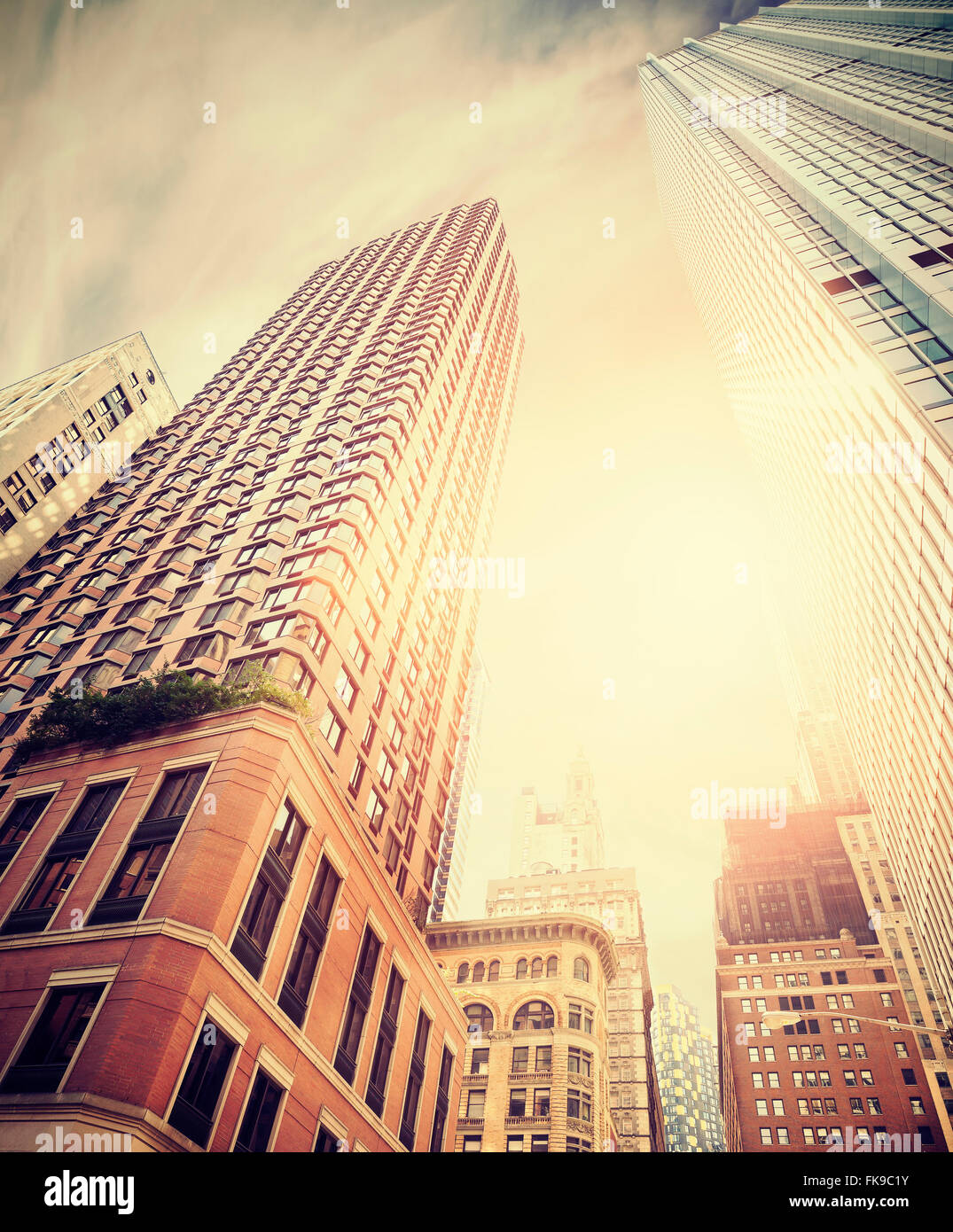Retro toned photo of Manhattan buildings against sun, New York City, USA. - Stock Image